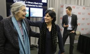 Massachusetts Institute of Technology astrophysics professor Nergis Mavalvala, center, celebrates with Rebecca Weiss, left, wife of MIT physics professor Rai Weiss, following an update by MIT scientists on gravitational waves, Thursday, Feb. 11, 2016, at MIT in Cambridge, Mass. In a blockbuster announcement, scientists said after decades of trying they have finally detected faint ripples of gravity reverberating invisibly through the fabric of both space and time, just as Einstein predicted. (AP Photo/Steven Senne)