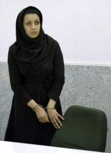 "A picture taken on July 8, 2007 shows Iranian Reyhaneh Jabbari standing handcuffed at police headquarters in Tehran after she was arrested for the murder of a former intelligence official. Jabbari who is awaiting an impending death sentence for slaying of former intelligence official Morteza Abdolali Sarbandi, could be forgiven if ""she tells the truth"", the victim's son said on April 19, 2014 as a UN human rights monitor claims the crime was done in self-defence against a potential rapist. AFP PHOTO/GOLARA SAJADIAN"