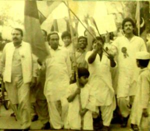 Fraz_Wahlah_as_a_Child_in_the_mid_80s_waving_Pakistan_Peoples'_Party_flag_whilst_leading_a_procession_against_the_Marshal_Law_and_dictatorship_of_General_Zia_ul_Haq_in_Pakistan,